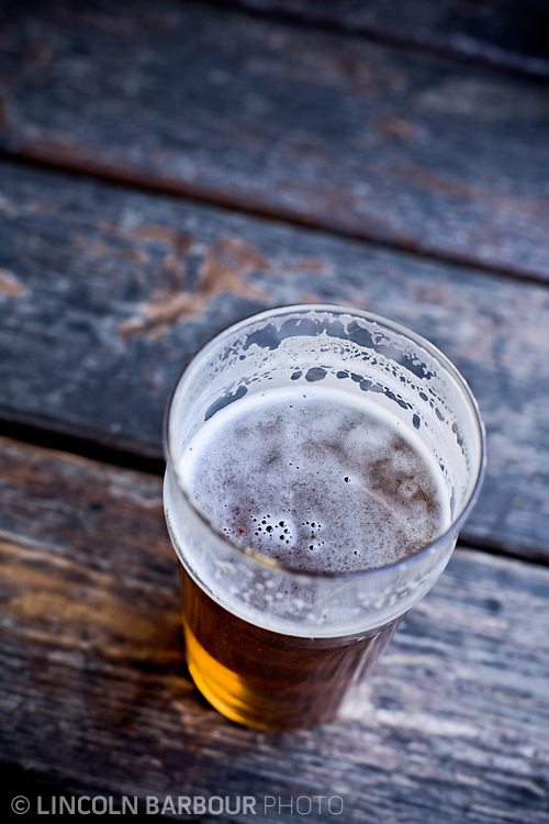A top down view of a dark colored beer on a picnic table, sipped down a little.