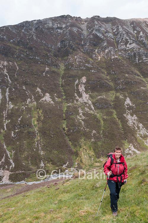 Walker ascending grassy slopes of Brackenthwaite Fell on Grasmoor