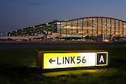 """An exterior view of Heathrow Airport's Terminal 5 building in West London. Created by the Richard Rogers Partnership (now Rogers Stirk Harbour and Partners). A lit airfield navigation taxiway sign shows the route number and code for pilots to find their way around the confusing network of taxiways and there are 1 million square metres of new apron and taxiway pavement for T5. At a cost of £4.3 billion, the 400m long T5 is the largest free-standing building in the UK with the capacity to serve around 30 million passengers a year. The Terminal 5 public inquiry was the longest in UK history, lasting four years from 1995 to 1999. From writer Alain de Botton's book project """"A Week at the Airport: A Heathrow Diary"""" (2009). ..."""