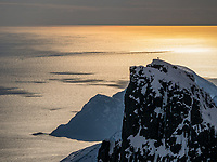 A skier has climbed the peak of Storstolpan in Troms, Arctic Norway. Now he is looking out over the meeting between the mountains and the large Norweigian Sea. The image is captured from the top of Hollendaren which is a few hundred meters higher than Storstolpan.