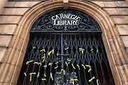 Yellow ribbons tied to the gates of the now closed Carnegie Library in Herne Hill, south London. The local community occupied their important resource for learning and social hub and after a long campaign but now Lambeth have gone ahead and closed the library's doors for the last time because they say, cuts to their budget mean millions must be saved. They plan to re-purpose it into a gym although details are unknown.