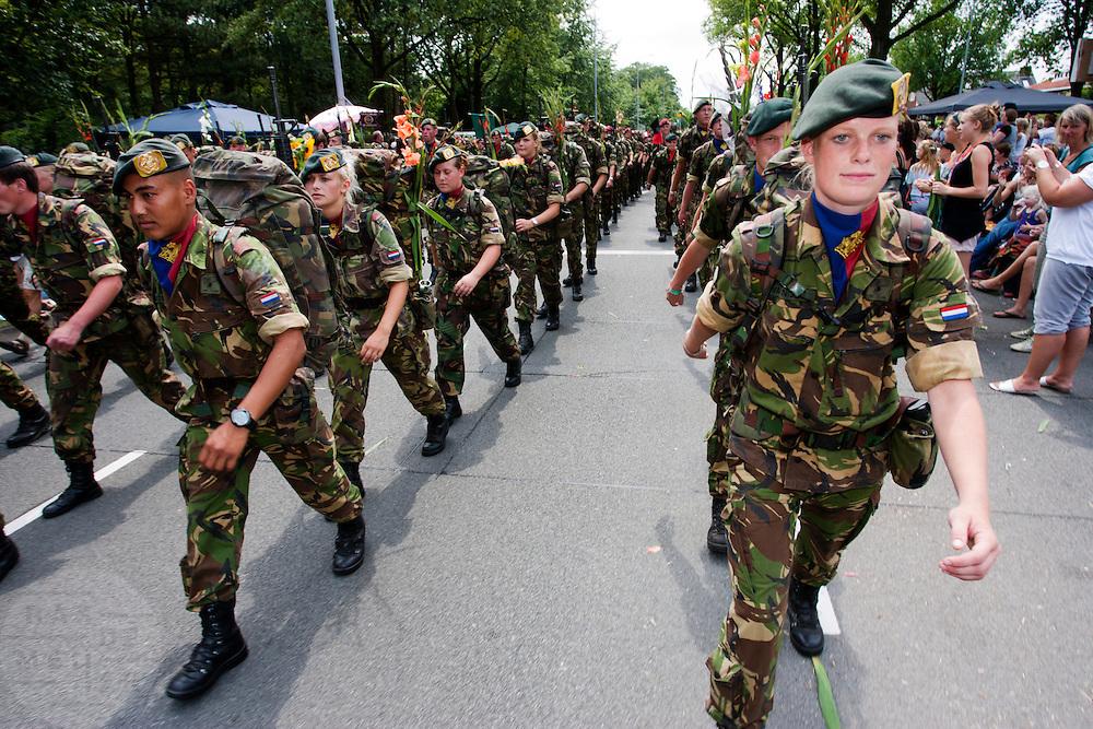 Nederlandse militairen lopen op de laatste dag van de Nijmeegse Vierdaagse over de Via Gladiola, zoals de Sint Annastraat is omgedoopt tijdens het wandelevenement.