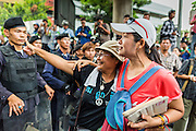 26 MAY 2014 - BANGKOK, THAILAND: Women taunt riot police during a protest against the coup in Thailand at Victory Monument during a pro-democracy rally in Bangkok. About two thousand people protested against the coup in Bangkok. It was the third straight day of large pro-democracy rallies in the Thai capital as the army continued to tighten its grip on Thai life.   PHOTO BY JACK KURTZ