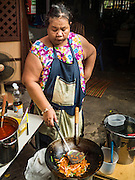 "27 AUGUST 2016 - BANGKOK, THAILAND: A woman cooks ""Pad Thai"" (fried Thai noodles) during a lunch for residents of the Pom Mahakan slum. The Pom Mahakan community is known for fireworks, fighting cocks and bird cages. Mahakan Fort was built in 1783 during the reign of Siamese King Rama I. It was one of 14 fortresses designed to protect Bangkok from foreign invaders. Only two of the forts are still standing, the others have been torn down. A community developed in the fort when people started building houses and moving into it during the reign of King Rama V (1868-1910). The land was expropriated by Bangkok city government in 1992, but the people living in the fort refused to move. In 2004 courts ruled against the residents and said the city could evict them. The city vowed to start the evictions on Sept 3, 2016, but this week Thai Prime Minister Gen. Prayuth Chan-O-Cha, sided with the residents of the fort and said they should be allowed to stay. Residents are hopeful that the city will accede to the wishes of the Prime Minister and let them stay.       PHOTO BY JACK KURTZ"