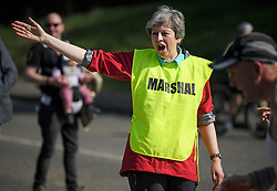 © Licensed to London News Pictures. 19/04/2019. Maidenhead, UK. Prime Minister THERESA MAY  helps out as a marshal at the Maidenhead Easter 10 run in her constituency of Maidenhead in Berkshire. Parliament currently on Easter recess after an extension to Article 50 was granted by the EU. Photo credit: Ben Cawthra/LNP