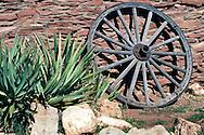 Old wooden wagon wheel against stone wall at Grand Canyon Village, Grand Canyon National Park, Arizona