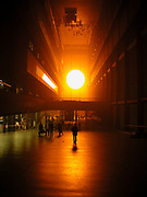 Public interact with the Weather Project by Danish artist Olafur Eliasson at Tate Modern. In this installation, representations of the sun and sky dominate the expanse of the Turbine Hall. A glance overhead reveals that the ceiling has disappeared, replaced by a mirror reflecting of the space below. This installation became so popular that numbers of visitors doubled.