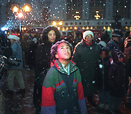 Trenton Bonds, 9, of South Bend, watches the snow falling Friday night in front of the Morris Civic Auditorium at a Christmas tree-lighting ceremony. About 4 inches had fallen as of Friday night and more is on the way.