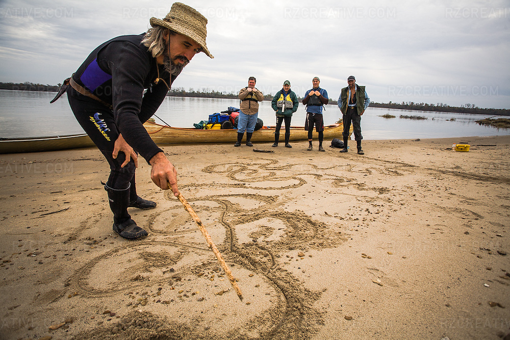 John Ruskey of Clarksdale, MS based Quapaw Canoe Company prepares to lead a group of paddlers on a 100-mile trip down the lower Mississippi River. Here, John draws the stretch of river they will paddle in the sand.