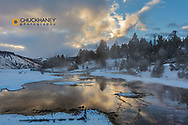 Sunrise clouds reflect into Grassy Spring in winter in Yellowstone National Park, Wyoming, USA