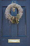 A low country style Christmas wreath made from Spanish Moss hangs from a wooden door on a historic home along the Battery in Charleston, SC.