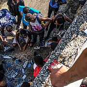 MYTILENE, GREECE - SEPTEMBER 12: Displaced asylum seekers gather to charge their phones in a ditch off the side of a road days after the Moria migrant camp fires, which started Tuesday night, and ended up burning most of the encampment on September 12, 2020 in Mytilene, Greece. According to UNHCR, current numbers say the asylum-seekers displaced from the encampment are around 12,000. (Photo by Byron Smith for CNN)