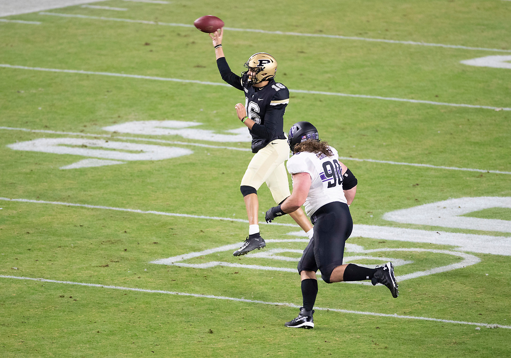 November 14, 2020:  Purdue quarterback Aidan O'Connell (16) passes the ball as Northwestern defensive lineman Jake Saunders (90) pursues during NCAA football game action between the Northwestern Wildcats and the Purdue Boilermakers at Ross-Ade Stadium in West Lafayette, Indiana. Northwestern defeated Purdue 27-20.  John Mersits/CSM.