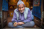 """An old Thangka painter from Bhaktapur, Nepal, is  smocking a cigarette on the entry of his shop. The hat on his head is called """"Dhaka Topi"""" and is usually given away as gifts during Dashain and Tihar festivals. <br /> Photo by Lorenz Berna"""