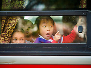 21 DECEMBER 2017 - HANOI, VIETNAM: Children in a school bus going to Ho Chi Minh's Mausoleum point at tourists outside their school bus in Hanoi.   PHOTO BY JACK KURTZ