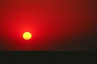 Red sky surrounds the setting sun, Saskatchewan prairie