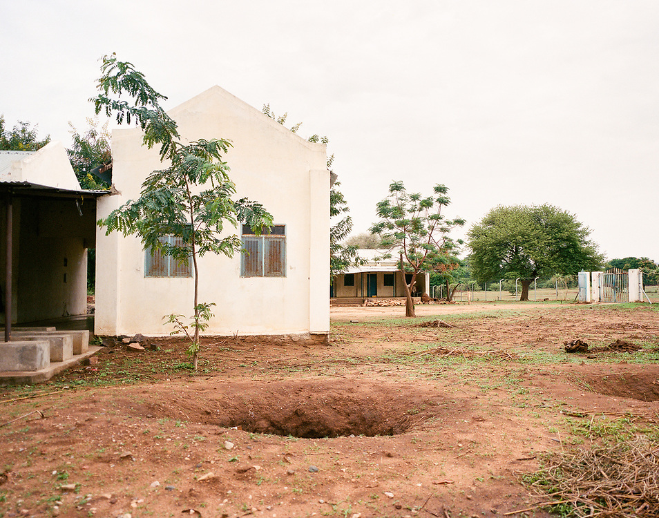 """NUBA MOUNTAINS, SUDAN – JUNE 9, 2018: A foxhole can be seen on the property of the former State Hospital in Kouda, where four parachute bombs were dropped in 2014. Miraculously, none of the ordinances exploded, and can still be seen protruding from the ground surrounding the hospital compound.<br /> <br /> In 2011, the government of Sudan expelled all humanitarian groups from the country's Nuba Mountains. Since then, the Antonov aircraft has terrorized the Nuba people, dropping more than 4,080 bombs on hospitals, schools, marketplaces and churches. Today, vestiges of the Antonov riddle the landscapes of daily life, where more than 1 million Nuba live in famine conditions – quietly enduring the humanitarian blockade intended to drive them out of the region. The skies are mostly clear. Yet the collective memory of the bombings remains an open wound, and the Antonov itself a persistent threat. So frequent were the attacks that the Nuba nicknamed the high flying aircraft and its dismal hum: """"Gafal-nia ja,"""" they would declare, running to the hillsides. """"The loss of appetite has come."""""""