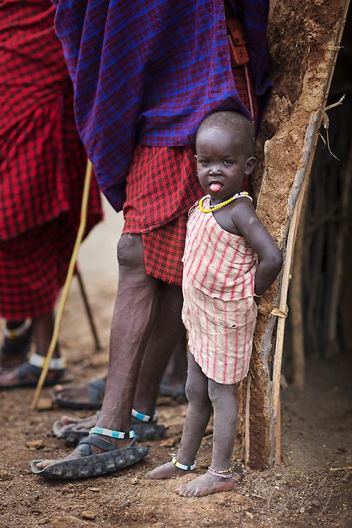 A Masaai toddler stands along side his father.