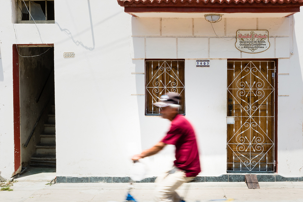 Man riding past facade of old house in Cienfuegos, Cuba