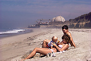 Nuclear Energy: A young couple with a baby lounges on the Pacific Ocean beach near the Nuclear Power Plant at San Onofre, California. (1986).