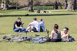 Licensed to London News Pictures. 19/04/2021. London, UK. Members of the public soak up the sunshine in Hyde Park, London a week after the easing of Covid-19 restrictions as a mini heatwave hit the UK this week with temperatures reaching up to 18c in London and the South East. Photo credit: Alex Lentati/LNP