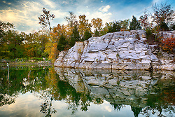 Rocky formations along the shore of Klondike Park Lake cast reflection along the waters' edge