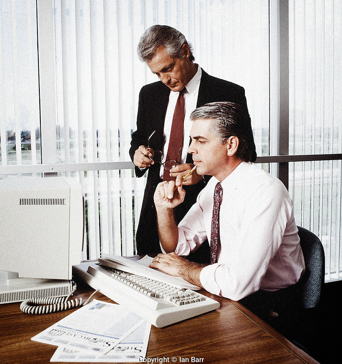 two execs with computer