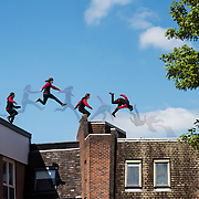 A composite image showing the path and movement of a parkour free runner moving over the roof tops.