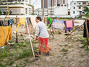 05 SEPTEMBER 2013 - BANGKOK, THAILAND:  A Cambodian woman who works on a construction site throws out dirty dish water after her shift at the construction site of a new high rise apartment / condominium building on Soi 22 Sukhumvit Rd in Bangkok. The workers live in the corrugated metal dorms on the site. Most of the workers at the site are Cambodian immigrants.             PHOTO BY JACK KURTZ