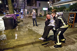 © licensed to London News Pictures. London, UK 27/02/2014. A woman being carried across the street where a burst main has flooded Clapham Road in south London on Thursday, 27 February 2014. Photo credit: Tolga Akmen/LNP