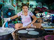 "08 JUNE 2017 - BANGKOK, THAILAND: A woman makes ""roti"" a type of flat bread, in Khlong Toey Market, Bangkok's main fresh market. Thai consumer confidence dropped for the first time in six months in May following a pair of bombings in Bangkok, low commodity prices paid to farmers and a sharp rise in the value of the Thai Baht versus the US Dollar and the EU Euro. The Baht is surging because of political uncertainty, related to Donald Trump, in the US and Europe. The Baht's rise is being blamed for a drop in Thai exports. This week the Baht has been trading at around 33.90 Baht to $1US, it's highest point in two years.      PHOTO BY JACK KURTZ"