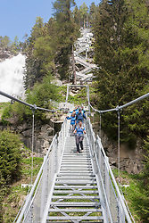 Group of climbers walking through suspension stairway, Stuibenfall Waterfall, Otztal, Tyrol, Austria