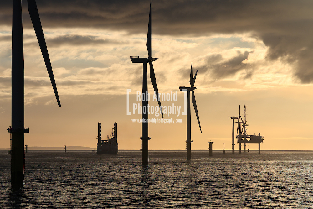 © Rob Arnold.  04/04/2014. North Wales, UK. Wind turbine installation vessels, Friedrich Ernestine (left) and Sea Worker (right) silhouetted by a bright orange sky at sunset over the Gwynt y Môr Offshore Wind Farm off the coast of North Wales. Photo credit : Rob Arnold