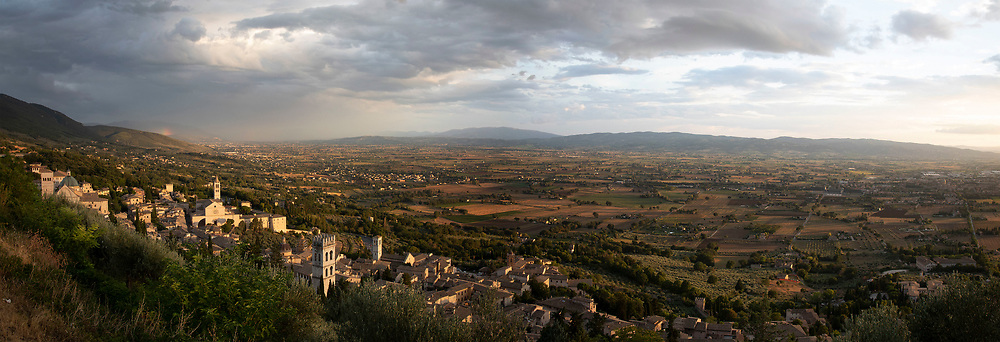 Panoramic view over the valley as rain falls south of Assisi, Umbria, Italy. Assisi is a town in the Province of Perugia in the Umbria region, on the western flank of Monte Subasio. It is generally regarded as the birthplace of the Latin poet Propertius, and is the birthplace of St. Francis, who founded the Franciscan religious order in the town in 1208, and St. Clare, Chiara dOffreducci, the founder of the Poor Sisters, which later became the Order of Poor Clares after her death. Assisi is now a major tourist destination for those sightseeing or for more religious reasons.