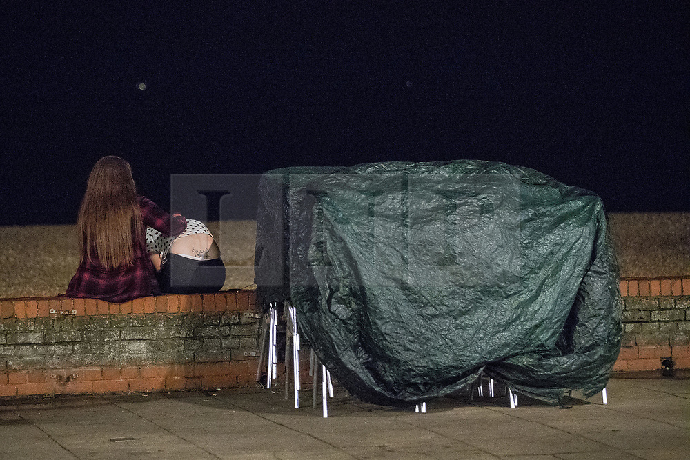 © Licensed to London News Pictures . 26/09/2017. Brighton, UK. A woman comforts a friend who is bent double sitting on a wall facing out to sea . Revellers at the end of a night out in Brighton during Freshers week , when university students traditionally enjoy the bars and clubs during their first nights out in a new city . Photo credit: Joel Goodman/LNP