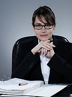 beautiful cheerful caucasian  business woman portrait sitting at desk on isolated background