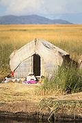 Woman sitting outside Reed house, Lake Titicaka, Puno, Peru, South America