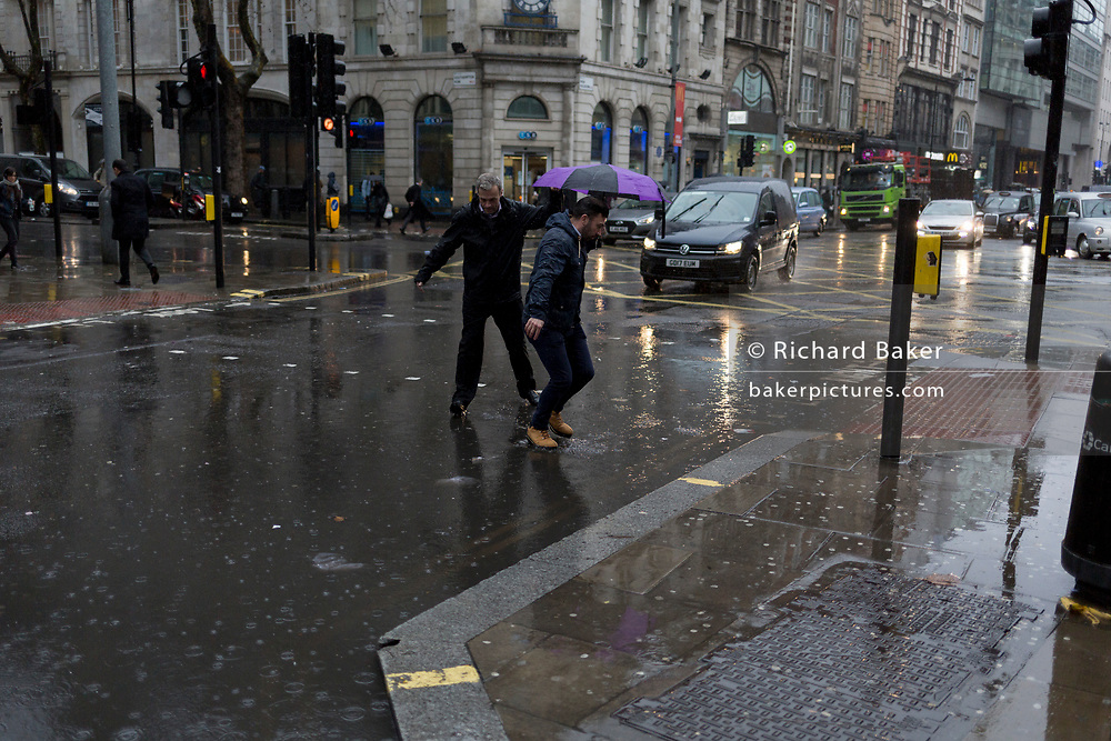 Storm Georgina swept across parts of Britain and in central London, lunchtime office workers were caught out by torrential rain and high winds, on 24th January 2018, in London, England. Pedestrians resorted to leaping across deep puddles at the junction of New Oxford Street and Kingsway at Holborn, the result of overflowing drains. First in a sequence of seven photos.