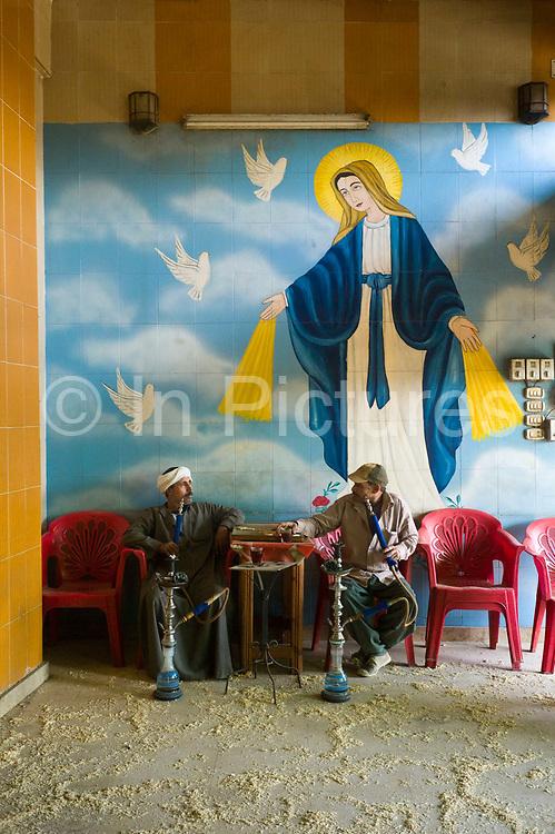 A man smokes a shisha pipe in the Qamar El Zaman coffeehouse in the Coptic Christian Zabbaleen area of Cairo, Egypt