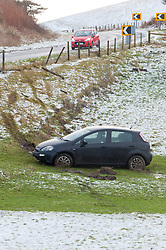 © Licensed to London News Pictures. 15/12/2019. Llanfihangel Nant Melan, Powys, UK. A car slides off the A44 near Llanfihangel Nant Melan in Powys, Wales, UK. Road conditions were treacherous after snow fell last night on high ground in Powys, Wales, UK. Photo credit: Graham M. Lawrence/LNP