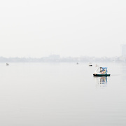 Paddle boats shaped as swans float on the calm waters of West Lake (Ho Tay) in Hanoi, Vietnam, on a hazy day.