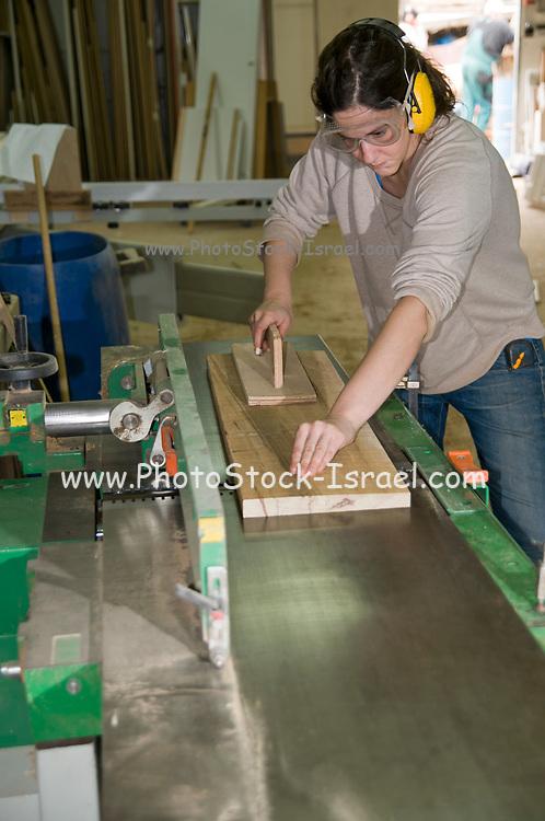 Female carpenter uses a powered carpenter's plane to flatten a plank of oak wood