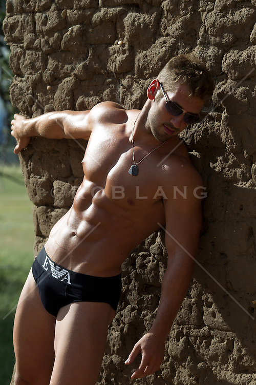 muscular man in briefs and sunglasses holding on to an adobe wall in New Mexico