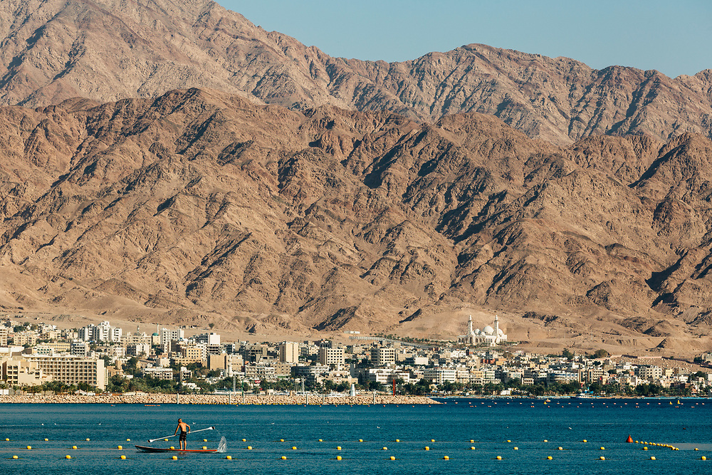 The Jordanian city of Aqaba and surrounding mountains provide the backdrop for a paddleboarder on the Red Sea in Eilat, Israel's southernmost city, at the northern tip of the Red Sea, on the Gulf of Aqaba, on March 14, 2018.