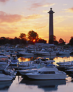 Sunrise silhouetting 352-foot Perry's Victory and International Peace Memorial standing beyond harbor at Put-in-Bay, South Bass Island, Lake Erie, Ohio