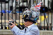 © Licensed to London News Pictures. 17/04/2013. Westminster, UK A man wearing a hat featuring pictures of Margaret Thatcher takes a photograph on the route. The hearse passes along Whitehall by the Cenotaph and Downing Street. The Funeral of former conservativePrime Minister Margaret Thatcher today 17th April 2013. Photo credit : Stephen Simpson/LNP