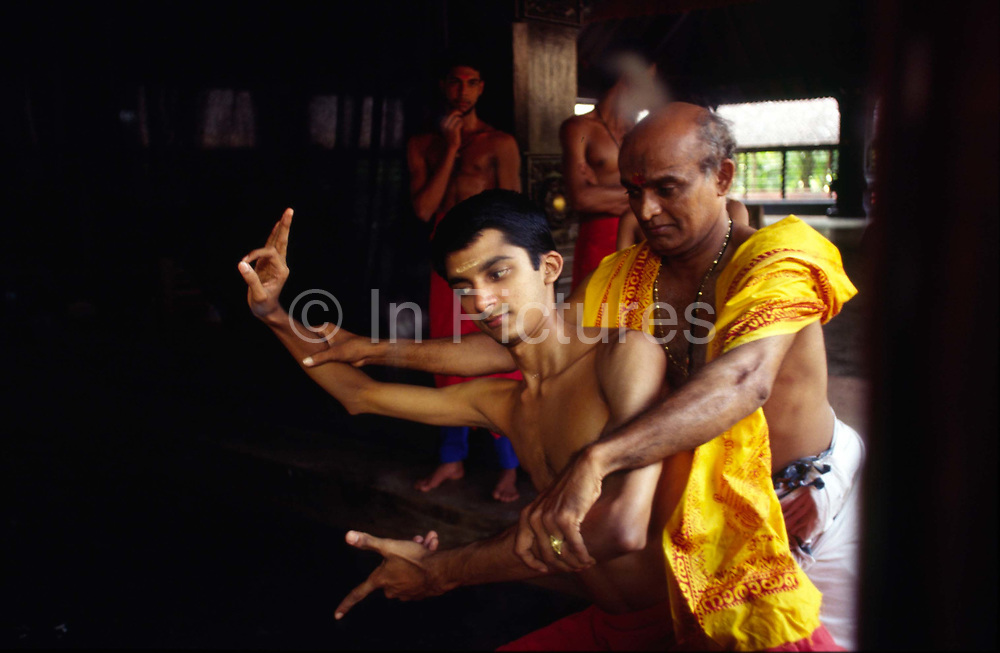 In a mirror, Professor Balasubramanian, a senior teacher of Kathakali shows a student a difficult step in class at the Kerala Kalamandalam.<br /> The Kalamandalam was founded in 1930 to preserve the cultural traditions of Kathakali, the stylised dance drama of Kerala. Kathakali is the classical dance-drama of Kerala, South India, which dates from the 17th century and is rooted in Hindu mythology. Kathakali is a unique combination of literature, music, painting, acting and dance performed by actors wearing extensive make up and elaborate costume who perform plays which retell in dance form stories from the Hindu epics.