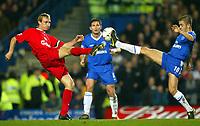 Photograph: Scott Heavey.<br /> Chelsea v Liverpool. FA Barclaycard Premiership.  07/01/2004.<br /> Sami Hyypia (L) and Joe Cole (R) go toe to toe as Frank Lampard looks on