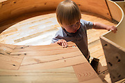 A boy engrossed by a circular table with continuous drawer, titled Round & Round, made by Luis Lim from reclaimed lumber. part of the 12 X 12 exhibit, itmes of reclaimed wood from 12 structures.