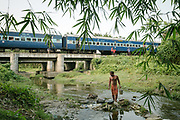 In West Bengal, a man bathes in a river near his home. Paley also had time to wash his own shirt before the train departed again.<br /> Outside the Dibrugarh-Kanyakumari Vivek Express, the longest train route in the Indian Subcontinent. It joins Kanyakumari, Tamil Nadu, which is the southernmost tip of mainland India to Dibrugarh in Assam province, near the border with Burma.
